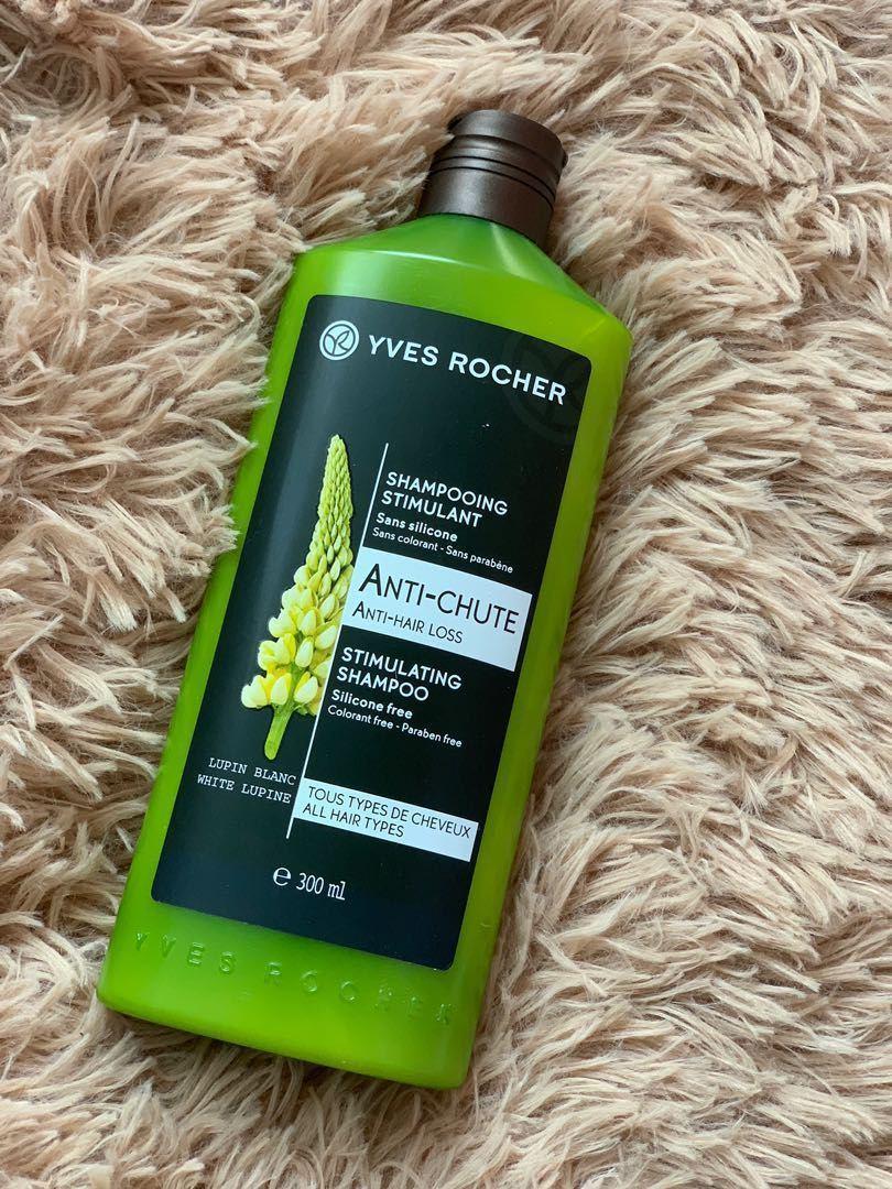 Dầu gội giảm rụng tóc Yves Rocher Anti Hair Loss Stimulating Shampoo có bao bì màu xanh lá cây, tem dán mặt trước in hình một nhành hoa Lupine trắng đẹp tinh tế, nổi bật (ảnh: internet).
